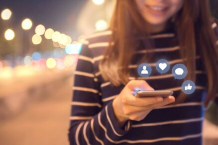 Woman Using Cell Phone to Like, Comment, Friend